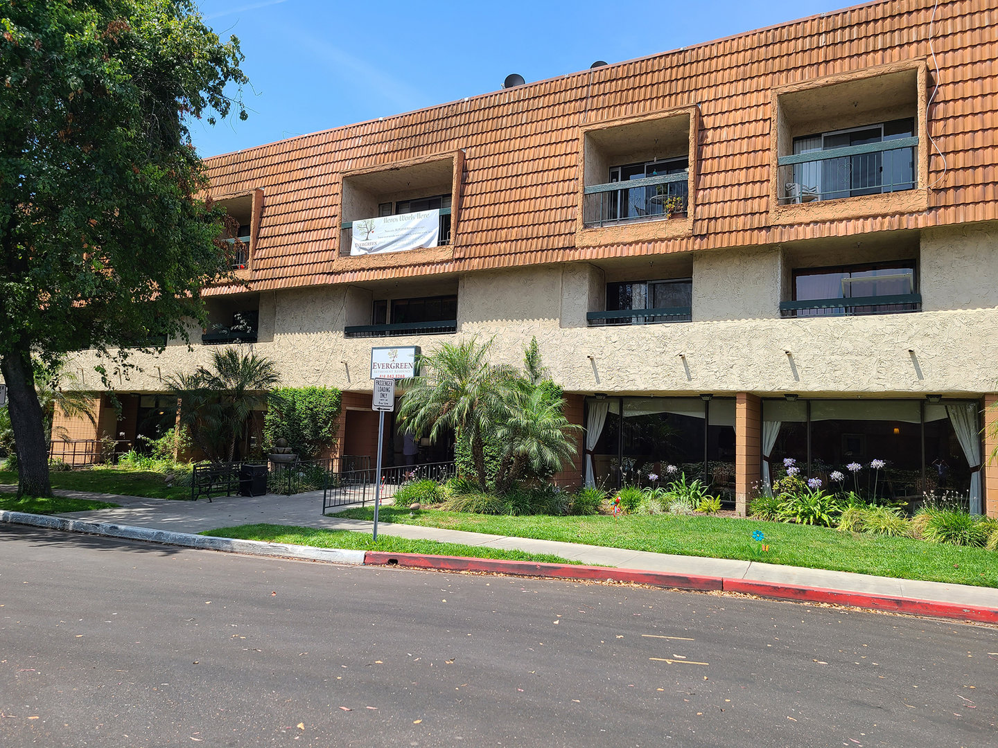 Evergreen Retirement Residence features balconies and a lawn adorned with trees and flowers.
